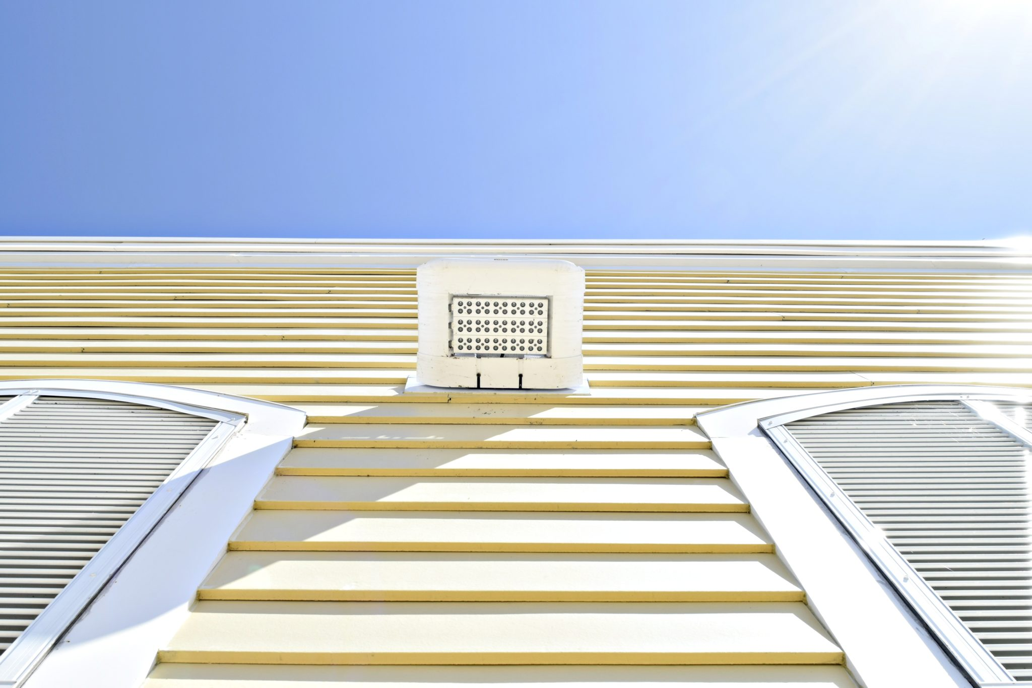 bright-tropical-yellow-siding-shutters-and-light-w-MN5XT68